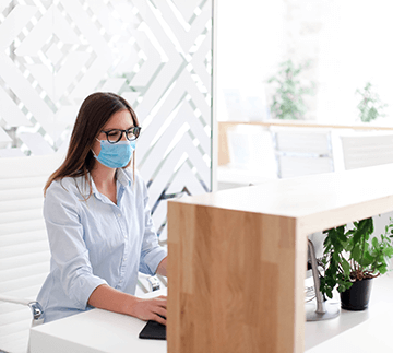 Receptionist wearing medical mask in office.